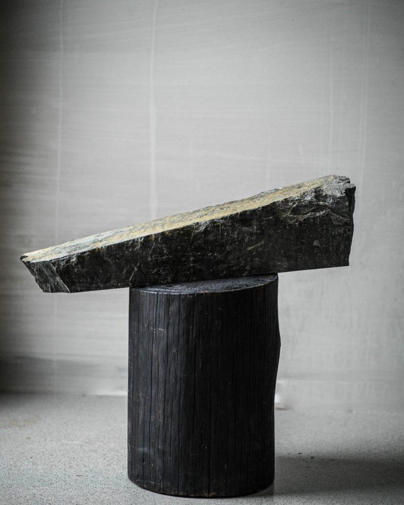 En skifermurstein som ligger på toppen av en trestubbe somet dekorativt objekt for å illustrere at norsk skifer, Ottaskifer, er bærekraftig